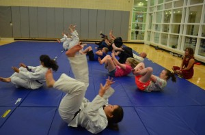 A beginners class with new students learning to roll and observing.